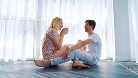 Lyckligt le förälskat sammanträde för par på golv och dricka morgonkaffe stock video