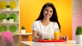 Lyckligt le f?r kvinna, magasin med sallad och ny orange fruktsaft p? tabellen, mellanm?lst?ng arkivfoto