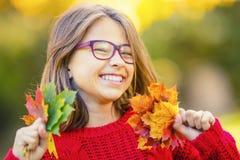 Lyckligt le för nedgångflicka och glade hållande höstsidor Härlig ung flicka med lönnlöv i röd kofta arkivfoto