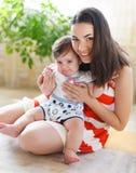 Lyckligt le fostrar med åtta gammala månad behandla som ett barn flickan Royaltyfria Bilder