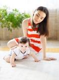 Lyckligt le fostrar med åtta gammala månad behandla som ett barn flickan Arkivfoto