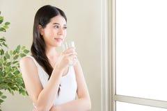 Lyckligt le kvinnadricksvatten med skönhet och bantar royaltyfria bilder