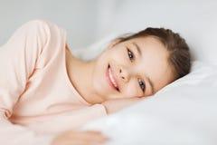Lyckligt le ligga för flicka som är vaket i säng hemma royaltyfri bild