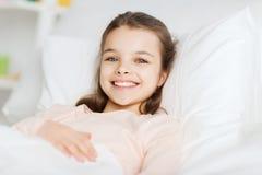 Lyckligt le ligga för flicka som är vaket i säng hemma royaltyfria bilder