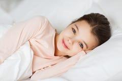 Lyckligt le ligga för flicka som är vaket i säng hemma royaltyfri foto
