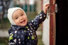 Lyckligt le litet barn i den vita woolen hatten som öppnar den gamla dörren till någonstans Barnsäkerhetsbegrepp royaltyfria foton