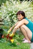 Lyckligt le mellersta arbeta i trädgården för ålderkvinna Royaltyfri Bild