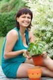 Lyckligt le mellersta arbeta i trädgården för ålderkvinna Royaltyfri Fotografi