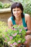 Lyckligt le mellersta arbeta i trädgården för ålderkvinna Arkivfoton