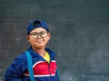 Lyckligt le och ställning för pojkekläderexponeringsglas framme av blackboen arkivfoton