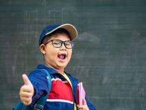 Lyckligt le och ställning för pojkekläderexponeringsglas framme av blackboen arkivbild