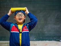 Lyckligt le och ställning för pojkekläderexponeringsglas framme av blackboen royaltyfri fotografi