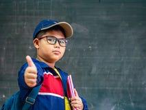 Lyckligt le och ställning för pojkekläderexponeringsglas framme av blackboen royaltyfri foto