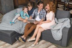 Lyckligt le sammanträde för dator för familjbruksminnestavla på soffan i sikten för bästa vinkel för vardagsrum, föräldrar som sp arkivbild