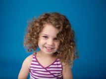 Lyckligt le skratta barn: Flicka med lockigt hår Arkivbild