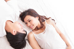 Lyckligt leende för par som till varandra ser i säng Royaltyfri Foto