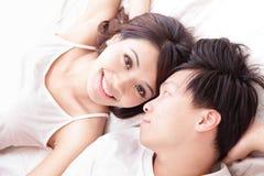 Lyckligt leende för par som till varandra ser i säng Royaltyfri Bild