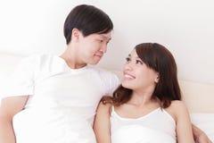 Lyckligt leende för par som till varandra ser i säng Royaltyfria Foton