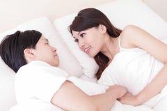 Lyckligt leende för par som till varandra ser i säng Arkivbild