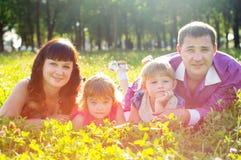 lyckligt ligga för familjgräs royaltyfri fotografi