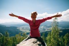 Lyckligt liten flickasammanträde på den steniga klippan i berget med mummel royaltyfria foton
