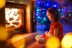 Lyckligt liten flickasammanträde vid en spis på julhelgdagsafton arkivfoto