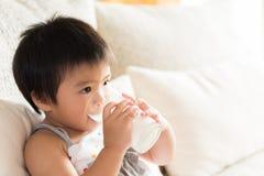 Lyckligt litet asiatiskt dricka för flickahandinnehav mjölkar exponeringsglas royaltyfri foto