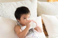 Lyckligt litet asiatiskt dricka för flickahandinnehav mjölkar exponeringsglas royaltyfri fotografi