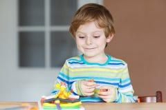 Lyckligt litet barn, förtjusande idérik ungepojke som spelar med deg Royaltyfri Bild