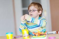 Lyckligt litet barn, förtjusande idérik ungepojke som spelar med deg Arkivfoto
