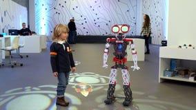 Lyckligt litet barn och stor robot på robotteknikfestival arkivfilmer