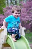 Lyckligt litet barn på en glidbana Arkivbild