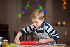 Lyckligt litet barn som förbereder kakor för jul och nytt år royaltyfri fotografi