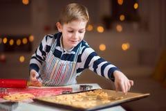 Lyckligt litet barn som förbereder kakor för jul och nytt år royaltyfria bilder