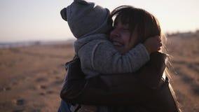 Lyckligt litet litet barn som kör till hennes moder som kramar på höststranden Gullig unge som kramar hans mamma, och dem som ner lager videofilmer