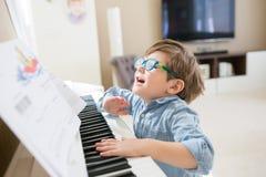Lyckligt litet barn som spelar pianot royaltyfri bild