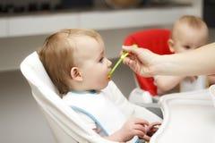 Lyckligt litet barnsammanträde i highchair och ätahavregröt Baby som lär att äta och, har yoghurt på havregröt royaltyfria foton