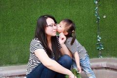 Lyckligt litet gulligt älskvärt behandla som ett barn den kinesiska barnkyssen för flickan och har gyckel med modermamman på somm arkivfoton