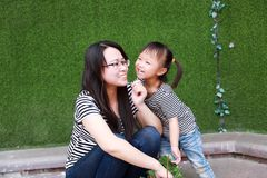 Lyckligt litet gulligt älskvärt behandla som ett barn den kinesiska barnkyssen för flickan och har gyckel med modermamman på somm arkivbild