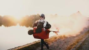 Lyckligt litet pilot- spela för flicka som kör längs solnedgångsjön i rolig pappnivådräkt med färgrökultrarapid arkivfilmer