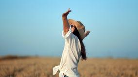 Lyckligt lopp som är kvinnligt i den vita skjortaresninghanden som tycker om frihet som omges av vetefältet stock video
