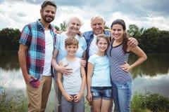 Lyckligt mång--utveckling familjanseende nära en flod royaltyfria foton