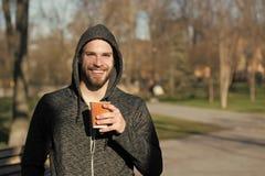 Lyckligt macho i kopp för kaffe för huvhåll disponibel i soligt parkerar Skäggigt manleende med den takeaway drinken på ny luft K arkivbilder
