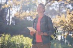 Lyckligt manligt fotvandrareanseende med den digitala minnestavlan i skog Royaltyfria Bilder