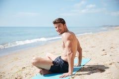 Lyckligt mansammanträde med ben korsade på stranden Royaltyfri Foto