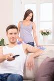 Lyckligt mansammanträde på hållande ögonen på tv för soffa Arkivbild
