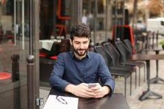 Lyckligt mansammanträde på kafétabellen och prata vid smartphonen med Fotografering för Bildbyråer