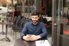 Lyckligt mansammanträde på kafétabellen och prata vid smartphonen med Royaltyfri Fotografi