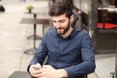 Lyckligt mansammanträde på kafétabellen och prata vid smartphonen med Royaltyfri Foto