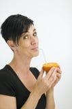 Lyckligt med apelsinen och sugrör Arkivbild